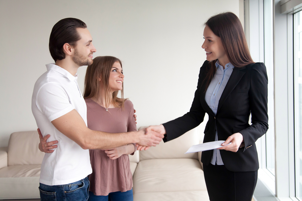 Smiling couple shaking hands with realtor
