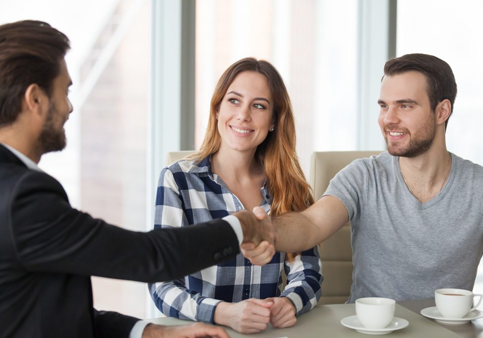 Happy couple handshaking a consulting agent in an office